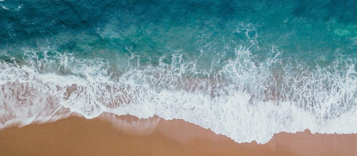 Waves hitting a beach shore.